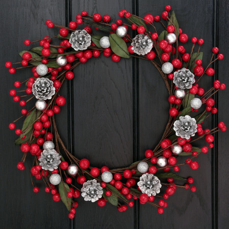 Christmas wreath with red and silver bauble decorations and pine cones over wooden background  photo