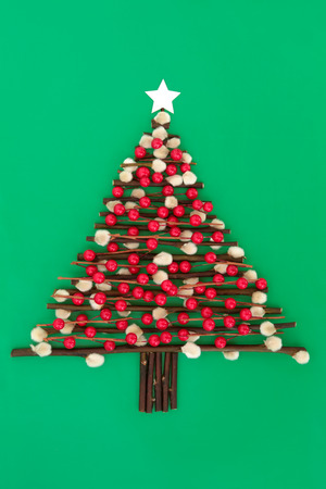 pussy tree: Abstract christmas tree design with red bauble decoration, pussy willow twigs and star over green paper background  Stock Photo