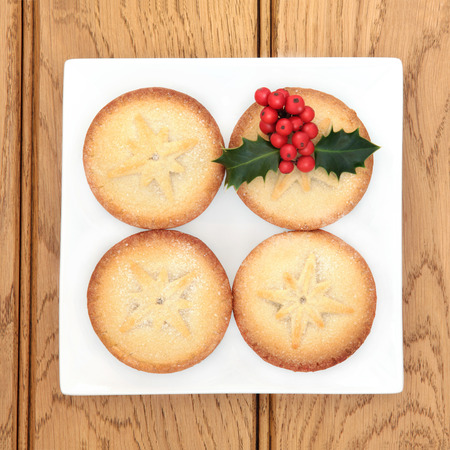 mince pie: Christmas mince pie cakes and holly on a plate over oak background