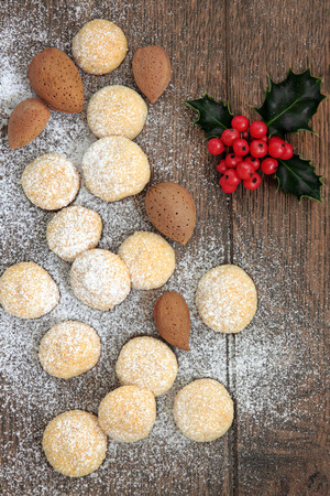 almond biscuit: Christmas almond biscuit background with nuts, holly leaf sprig and icing sugar over old oak wood background