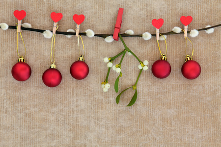 brown pussy: Christmas red bauble decorations with mistletoe leaf sprig hanging on a pussy willow branch over brown paper background