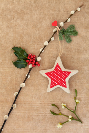 brown pussy: Christmas abstract with star decoration, holly and fir hanging on a pussy willow branch with mistletoe over old brown paper background