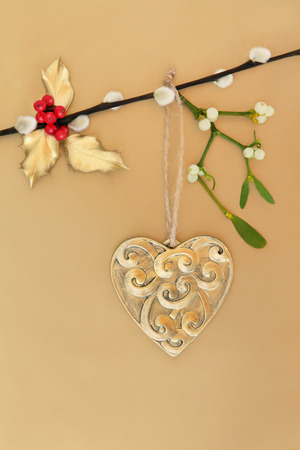 christmas pussy: Heart shaped christmas bauble with mistletoe and holly leaf sprigs hanging on a pussy willow branch over gold paper background