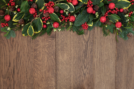 backround: Christmas background border with red bell baubles, fir, holly, ivy, mistletoe and cedar cypress with pine cones over old oak