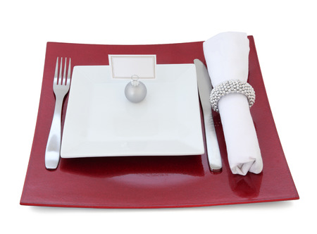 napkin ring: Christmas dinner place setting with plate, cutlery, name tag on bauble and serviette with silver napkin ring over white background