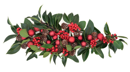 floral arrangements: Christmas floral decoration of holly, red baubles and pine cones over white background  Stock Photo