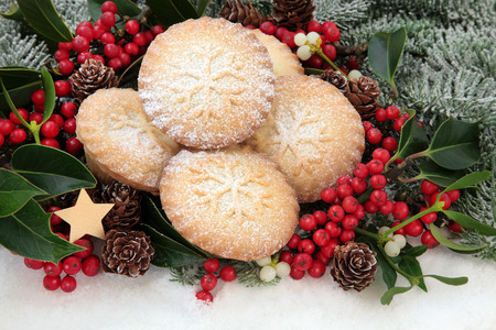 Christmas mince pie cakes with holly, mistletoe and snow covered fir  Stock Photo