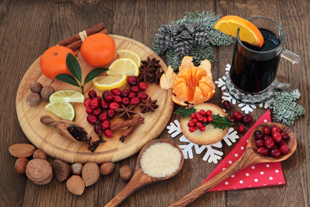 mince pie: Christmas food with mulled wine ingredients of citrus fruit and spices with nuts and mince pie over oak background