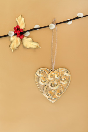 christmas pussy: Christmas heart shaped gold bauble with mistletoe and holly leaf sprigs hanging on a pussy willow branch