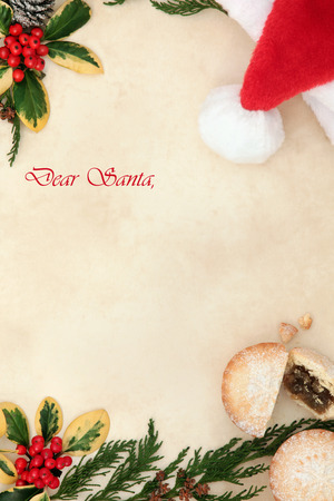 mince pie: Christmas eve letter to santa with red hat, mince pie, holly, cedar cypress and pine cones over old parchment