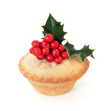 Mince pie with holy berry leaf sprig over white background
