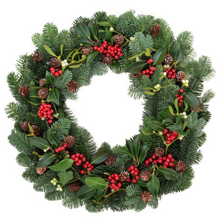 spar: Winter en kerst bloemen krans met hulst, klimop, maretak en sparren spar op een witte achtergrond Stockfoto
