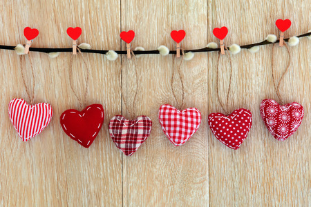 christmas pussy: Red heart shaped christmas decorations hanging on a pussy willow branch with pegs over old oak wood background