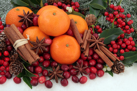christmas spice: Cranberry and mandarin orange christmas fruit with cinnamon and star anise spice, holly, mistletoe, ivy and snow covered fir