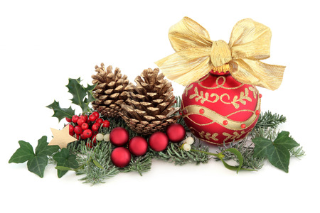 Christmas decoration with holly, red baubles, mistletoe, ivy, fir and cedar leaf sprigs with gold pine cones over white background