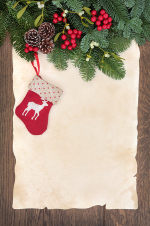 Christmas stocking decoration with winter greenery border over parchment and oak background   photo