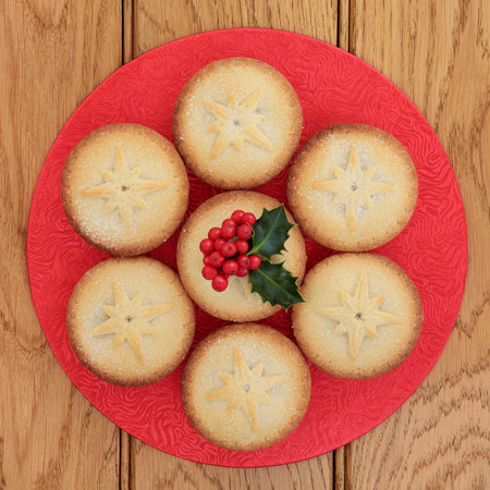 mince pie: Mince pie cakes and holly over oak background