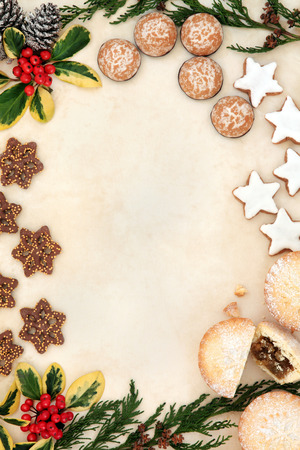 Christmas gingerbread biscuit selection and mince pie cakes forming a background border of holly and winter greenery over old parchment paper.