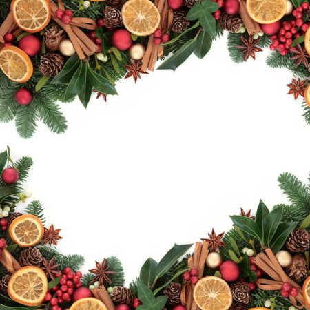 Christmas dried orange fruit with cinnamon and star anise spice, holly, mistletoe, pine cones, fir and snow.