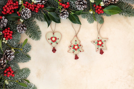old fashioned christmas: Old fashioned christmas tree decorations with winter floral border of fir, holly, mistletoe and pine cones with snow over old parchment background. Stock Photo