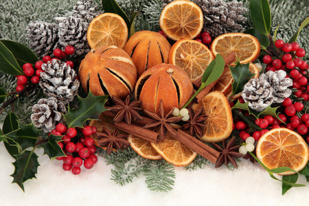 cinammon: Christmas dried orange fruit with cinammon and star anise spice, holly, mistletoe, pine cones, fir and snow.