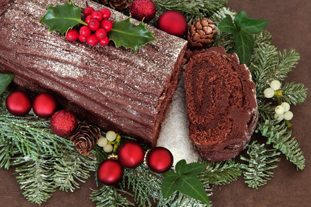 Chocolate yule log cake with red bauble decorations, holly, ivy, mistletoe and snow covered fir over brown handmade lokta paper background.