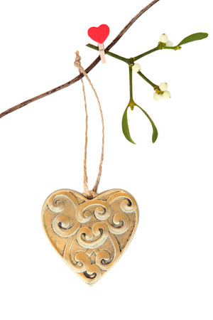solstice:  Christmas gold heart shaped decoration with mistletoe leaf sprig hanging on a string line over white background.
