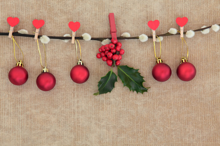 christmas pussy: Christmas red bauble decorations with holly hanging on a pussy willow branch over old brown paper background. Stock Photo