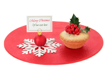 mince pie: Christmas mince pie cake with holly and red bauble with name place setting tag over white background. Stock Photo
