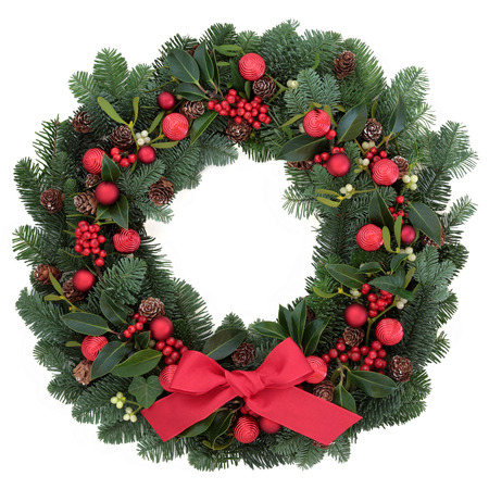 christmas wreath: Christmas wreath with red bauble decorations and bow, holly, ivy, mistletoe, fir and pine cones over white background. Stock Photo