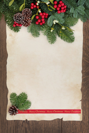 parchments: Merry christmas background border with fir, red berry sprays, mistletoe and pine cones over old parchment paper and oak wood. Stock Photo