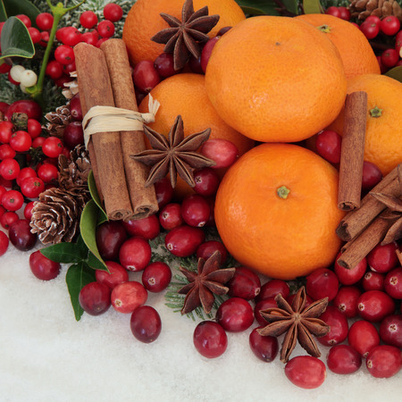 cinammon: Cranberry and mandarin orange christmas fruit with cinammon and star anise spice, holly, mistletoe, ivy and snow. Stock Photo