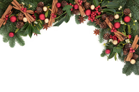 Christmas background border with cinnamon stick spice, bauble decorations, holly, ivy, mistletoe and fir over white with copy space. photo
