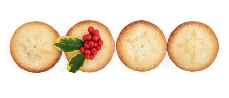 mince pie: Christmas mince pie cakes and holly in a line over white background.