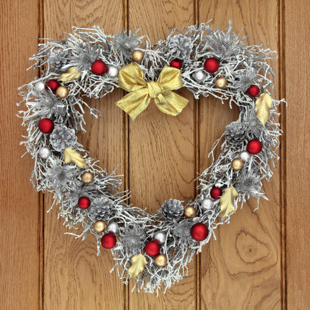 heart shaped christmas wreath with red gold and silver bauble decorations over old oak background - Red Gold And Silver Christmas Decorations