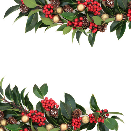 Christmas background border decoration with holly, baubles and pine cones over white background.