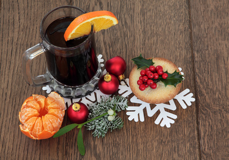 mince pie: Christmas mulled wine with mince pie, red bauble decorations and winter flora over oak background.