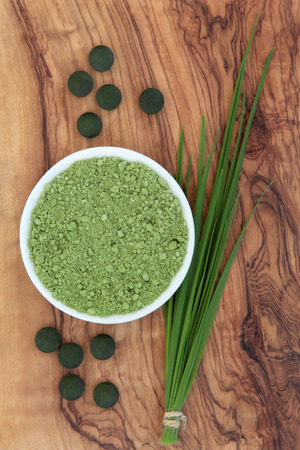 Chlorella tablets, spirulina powder and wheat grass over olive wood background. photo