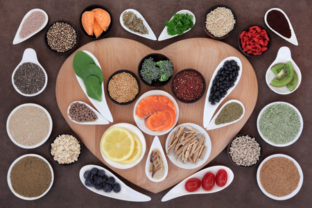Super health food selection in bowls on a heart shaped board over lokta paper background.
