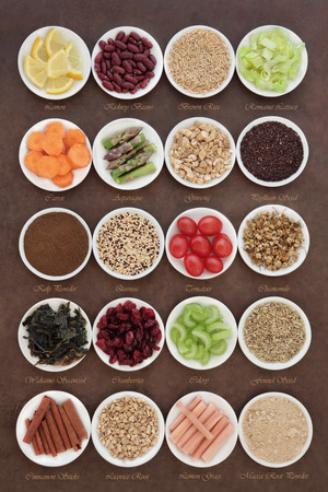 Large diet health food selection in porcelain bowls over lokta paper background. With titles. photo
