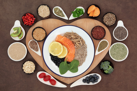 Large health food selection in bowls on a heart shaped wooden board over lokta paper background. photo