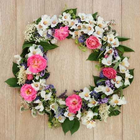 philadelphus: Summer flower wreath over light oak background. Stock Photo