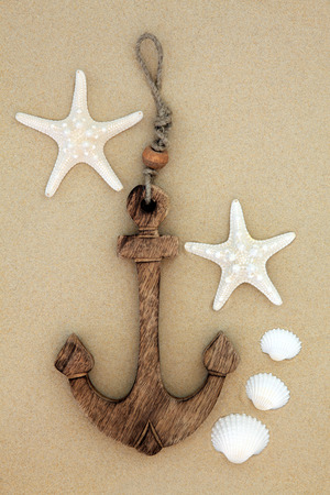 Starfish and cockle shells with decorative anchor on beach sand background. photo