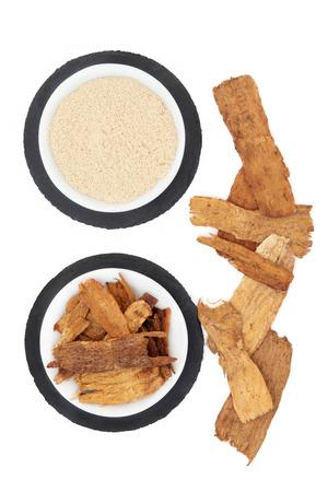 Hierba astrágalo y polvo utilizado en la medicina herbal China sobre fondo blanco. Foto de archivo