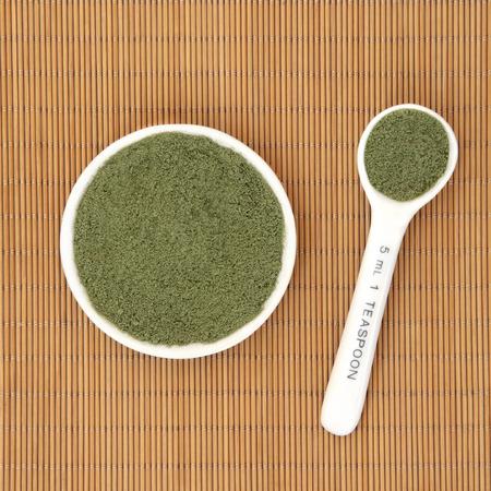 oleifera: Moringa ole�fera hierba en polvo medicina alternativa ayurveda y s�per alimento en un recipiente de porcelana blanca y una cuchara de medici�n sobre el fondo de bamb�.