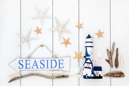 Seaside sign, starfish shells, driftwood and decorative lighthouse over wooden white background. photo