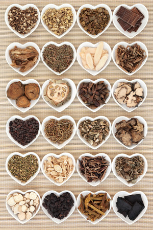 Large chinese herbal medicine selection in heart shaped porcelain bowls over bamboo background. photo