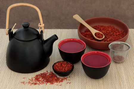 tea strainer: Safflower herb tea also used in chinese herbal medicine, teapot, cups and strainer on bamboo.