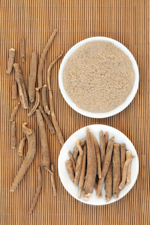 plant antioxidants: Ginseng ashwagandha herb root and korean powder over bamboo background. Stock Photo