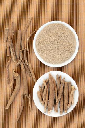 Ginseng ashwagandha herb root and korean powder over bamboo background. Archivio Fotografico